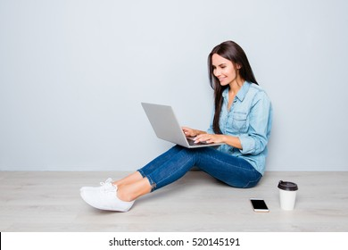 Young smiling woman working on laptop while sitting on floor