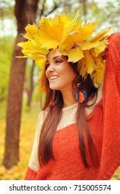 Young smiling woman with wreath of maple leaves on a head, outdoor portrait in autumn park