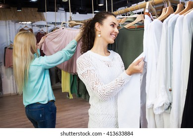 Young smiling women buying dress in clothing store