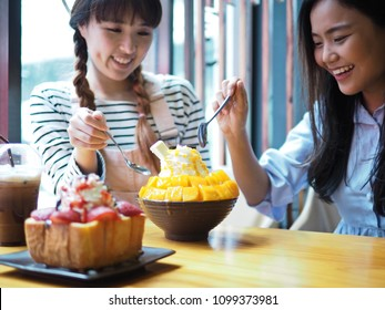Young smiling women holding spoon to eat Mango Bingsu (Bingsoo) Korean shaved ice dessert topped with diced mango and cheese. Blurred foreground of strawberry chocolate brick toast and iced coffee.