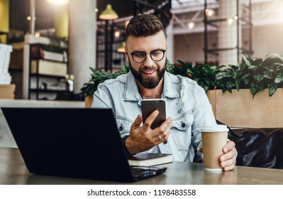 Young smilingbearded businessman is sitting, drinking coffee, using smartphone. Freelancer work in cafe. Hipster man blogging.On table is laptop.Social media. Man learning online.Education for adilte.