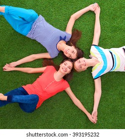 Young smilling women lying on green grass