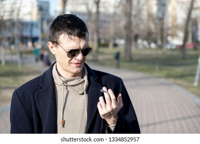 Young smoker man with sunglasses holding smoking cigarette in his hand ad looking with disgust facial expression and bad taste in his mouth