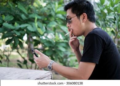 Young Smoker is smoking and playing the mobile