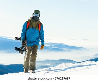 Young snowboarder in helmet walking at the very top of a mountain with his snowboard in hand