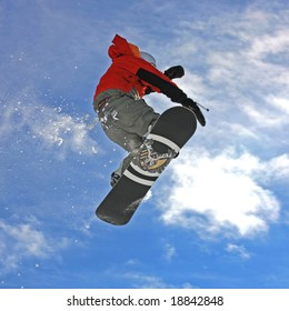 Young snowboarder jumping high in the air