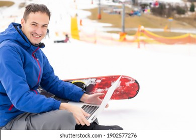 Young snowboarder using laptop on snowy mountain. White snow and blue sky. Copy space for advertisement.