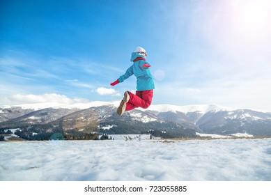 young snowboarder woman jumping over the slope in winter