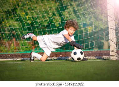 Young soccer goalie attempting to make a save. little soccer goalkeeper with gloves. Kids - soccer champion. Boy goalkeeper in football sportswear on stadium with ball. Sport concept.