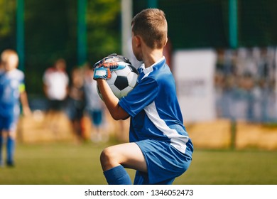 Young Soccer Goalie Goalkeeper Catching Ball. Young Boy Soccer Goalie. Soccer Game on Sunny Summer Day. Sport Activities for Children. Football Match in the Background. Youth Sport Wallpaper