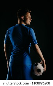 Young soccer player with ball on black background in studio. football player with a stylish haircut. Back view. Blue shirt.
