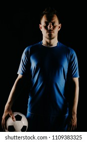 Young soccer player with ball on black background in studio. football player with a stylish haircut.