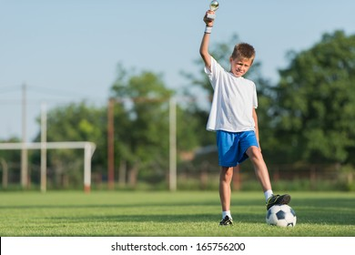 Young soccer player with his new trophy