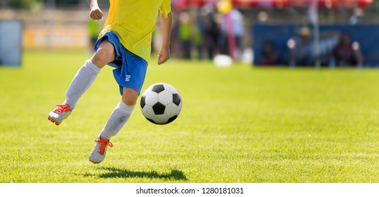 Young Soccer Player Kicking Ball. Horizontal Football Match Image with Blurred Pitch in the Background