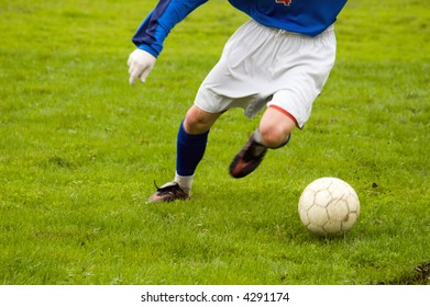 young soccer player kicking during a game