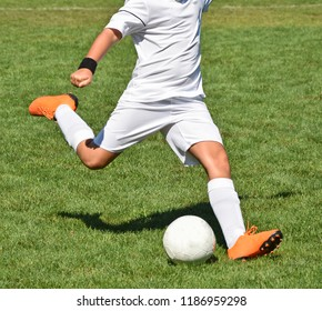Young soccer player kicks the ball