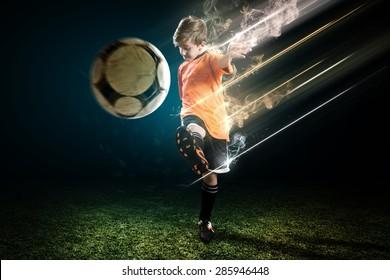 Young Soccer player kicks the ball