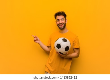 Young soccer player man pointing to the side with finger