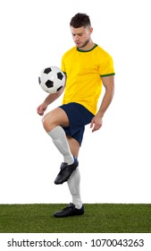 Young soccer player on grass with yellow and green shirt kicking a ball on white background