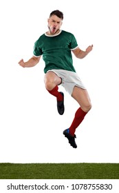 Young soccer player on grass with green shirt jumping and screaming with emotion on white background