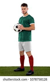 Young soccer player on grass with green shirt and ball in hands on white background