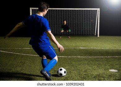 Young soccer player taking a penalty kick against a blurred goalkeeper in the goal