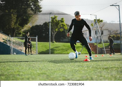 Young soccer player training in football field with team in background. Five a side football team practicing on field outdoors.