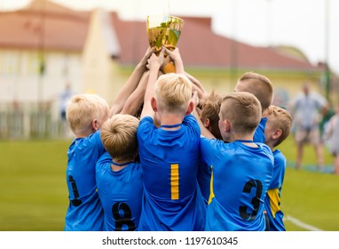 Young Soccer Players Holding Trophy. Boys Celebrating Soccer Football Championship. Winning team of sport tournament for kids children teams.