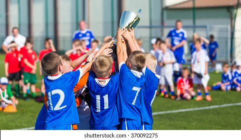 Young Soccer Players Holding Trophy. Boys Celebrating Soccer Football Championship. Winning team of sport tournament for kids children. Horizontal sport background.