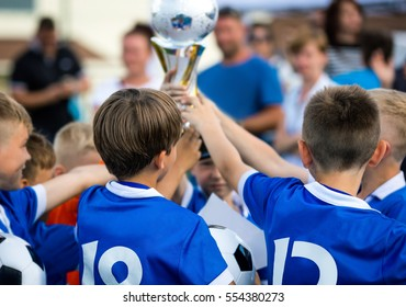 Young Soccer Players Holding Trophy. Children Soccer Football Champions.  Boys Celebrating Soccer Championship. 772836598e