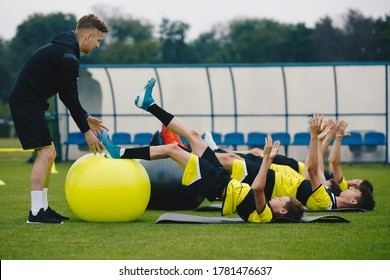 Young Soccer Players in Team on Training with Coach. Boys Training with a Gym Ball. Stability Training On Junior Male Soccer Team. Coach Instructs Players How to Exercise with Gym Balls Properly