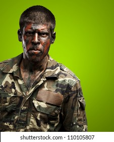 young soldier with camouflage paint looking very serious over green