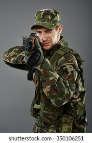 Young soldier with camouflage uniform aiming the target, studio shoot