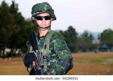 Young soldier, holding a rifle, wore dark glasses.