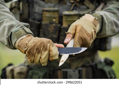 young soldier with a knife cut a wooden stick