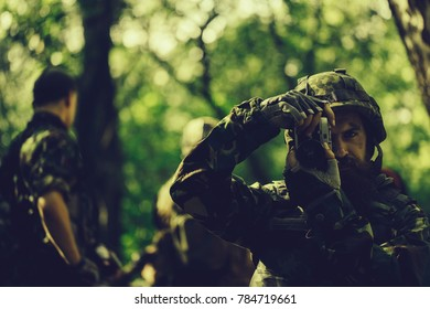 Young soldier man with beard on grime serious face in army ammunition and helmet holding camera in his hands on background of soldiers in forest