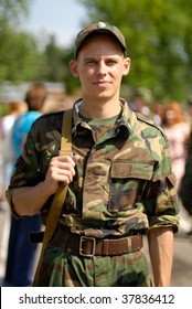 Young soldier poses with some civilians in the blurred out-of-focus background