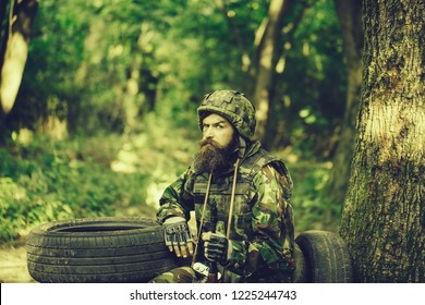 Young soldier wirh bearded dusty tired face in military camouflage uniform with hanging camera and rifle in hand sitting on guard near tree and black tyres in forest.