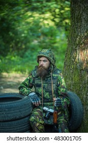 Young soldier wirh bearded dusty tired face in military camouflage uniform with hanging camera and rifle in hand sitting on guard near tree and black tyres in forest