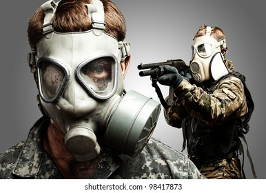 young soldiers wearing gas mask over grey background