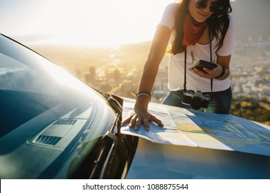 Young solo traveler looking at mobile phone and tourist map on car hood. Young female tourist on a road trip searching for directions.