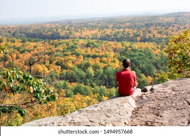 Young solo traveler sitting on a steep rock, admiring panoramic view of autumn forest and Ottawa Valley. Hiking along Skyline and King Mountain Trail, Gatineau Park, Canada. Rear view
