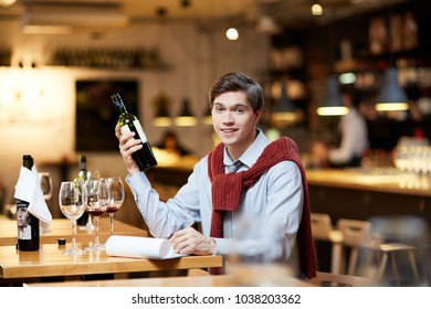 Young sommelier choosing a bottle of good wine at restaurant