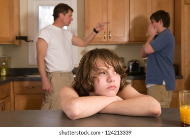 Young son sulks as father scolds his older brother