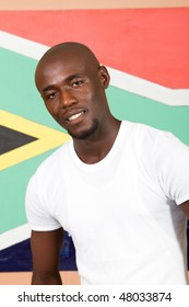 young South African man in front of South African flag smiling,