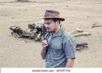 Young south african wildlife ranger with walkie talkie sends information about found dead body of a giraffe to the headquarter.