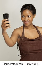 Young South African woman taking a picture of herself with her phone.
