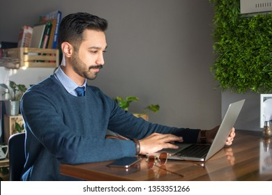 Young south asian man using laptop in office