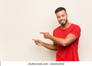 Young south-asian man excited pointing with forefingers away.