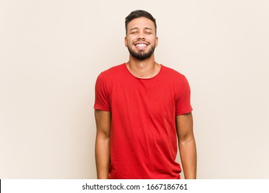 Young south-asian man laughs and closes eyes, feels relaxed and happy.